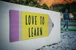Wall with a pencil painted in which is written Love to learn starting with words in Tahitian